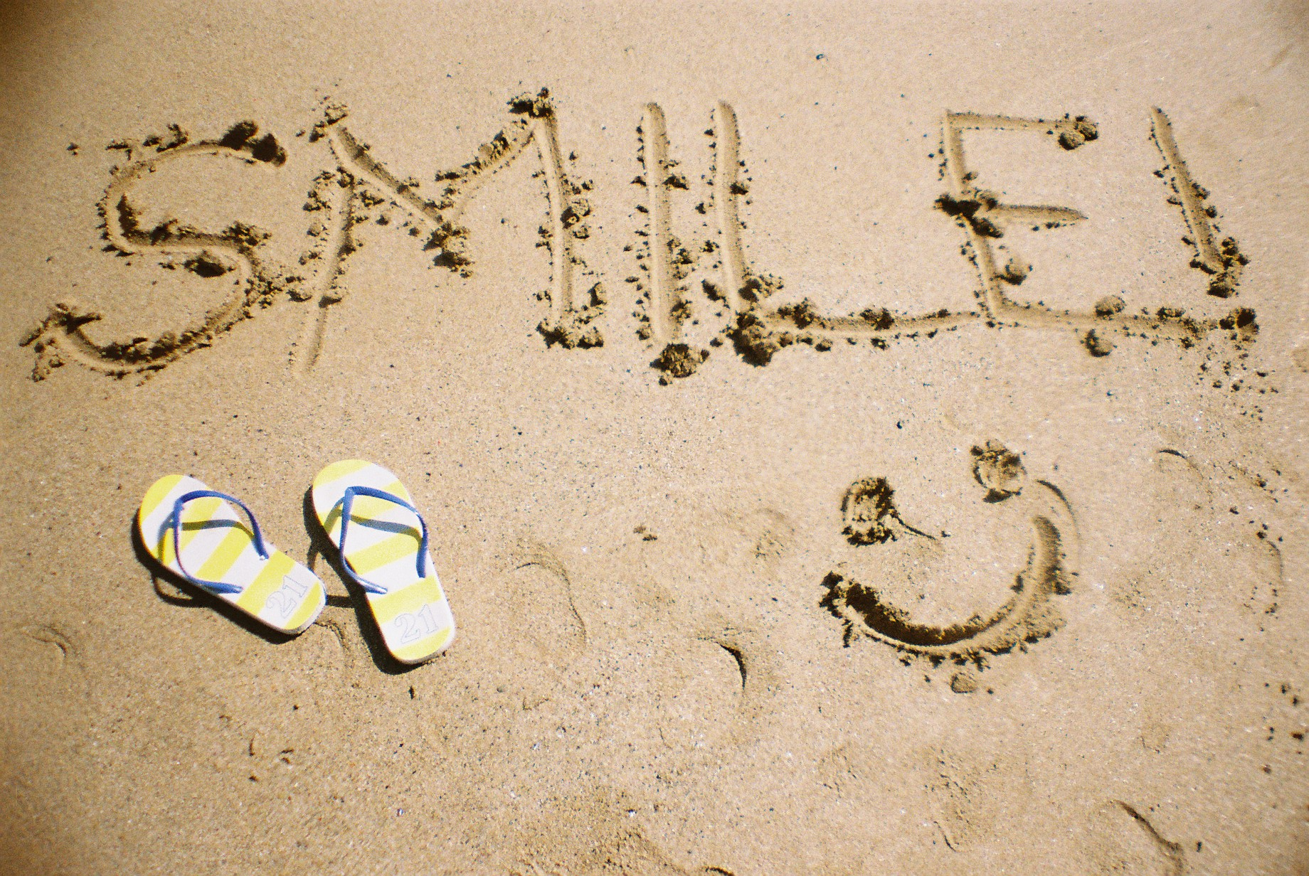 'Smile' written in the sand